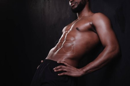 cropped shot of muscular shirtless man standing with hands on waist on black