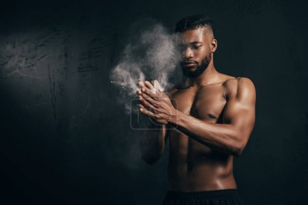 young bare-chested african american sportsman applying talcum powder on hands on black