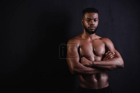 handsome muscular african american man standing with crossed arms and looking at camera on black