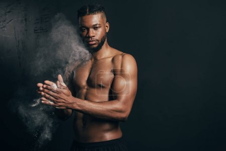 Photo for Young bare-chested african american sportsman applying talcum powder and looking at camera on black - Royalty Free Image