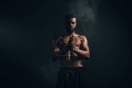 young african american sportsman applying talcum powder and looking at camera on black