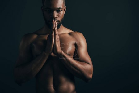 serious shirtless young african american sportsman looking at camera isolated on black