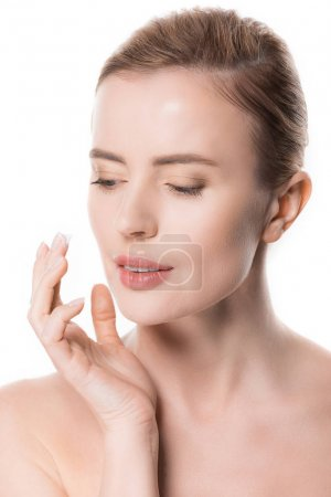 Portrait of woman applying cream on face isolated on white