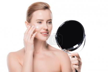 Woman applying cream on face while looking at mirror isolated on white