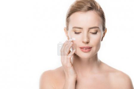 Female with closed eyes applying cream on her face isolated on white