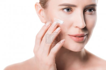 Female applying cream on face isolated on white