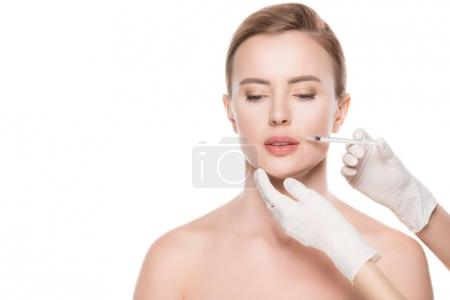 Photo for Beautician hands doing injection in woman lips isolated on white - Royalty Free Image