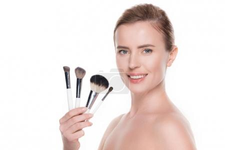 Smiling woman with cosmetic brushes isolated on white