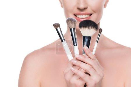 Photo pour Vue recadrée d'une femme à peau propre tenant des pinceaux cosmétiques isolés sur du blanc - image libre de droit