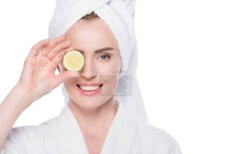 Female with clean skin holding slice of lime isolated on white