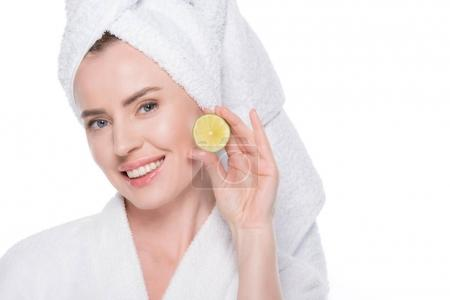 Woman with clean skin holding slice of lime isolated on white