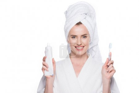 Woman with clean skin holding tootbrush and toothpaste isolated on white