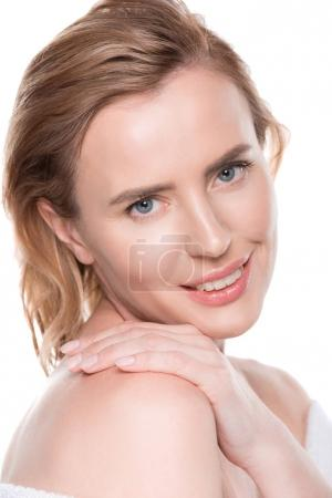 Smiling woman with clean skin touching own shoulder isolated on white