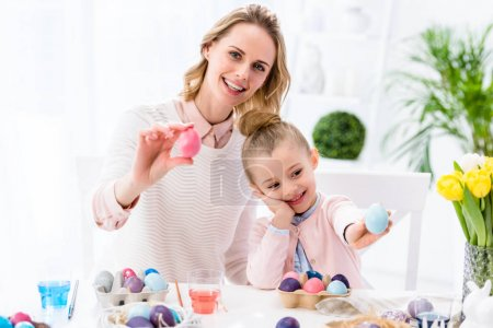 Mother and daughter showing colored Easter eggs