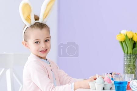 Photo for Child girl playing wearing bunny ears by table with Easter colored eggs - Royalty Free Image