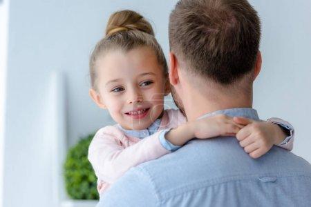 Cute preadolescent daughter embracing father