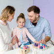 Parents and daughter by table with painted Easter eggs