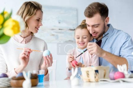 Photo for Smiling family with daughter coloring chicken Easter eggs - Royalty Free Image