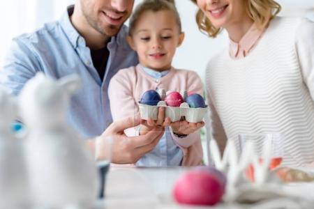 Smiling family holding Easter eggs