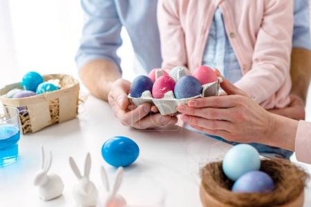Carton with Easter colored eggs in hands of family with daughter