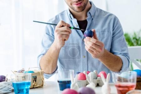 Close-up view of man painting Easter eggs
