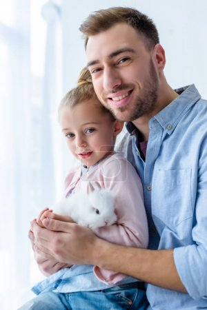 Father and child girl holding white bunny