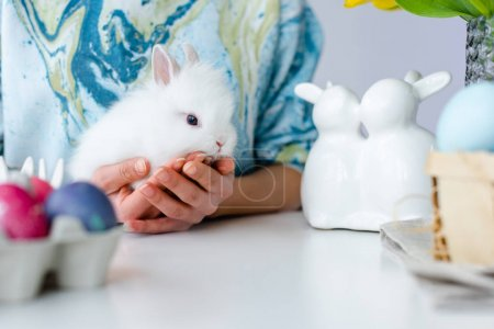 Photo for Easter bunny in female hands with eggs on table for Easter - Royalty Free Image