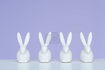 Rabbit statuettes in row on violet background
