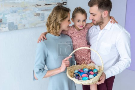 Parents and daughter with basket with Easter eggs