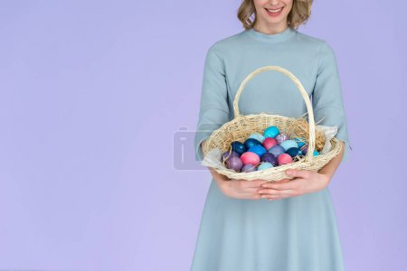 Woman with painted Easter eggs in basket isolated on violet