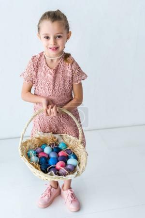Child girl holding Easter eggs in basket