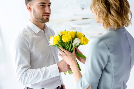 Woman receiving tulips from smiling man on 8 march