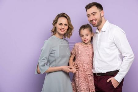 Adorable family with daughter isolated on violet