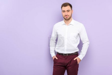 Man wearing shirt standing with hands in pockets isolated on violet