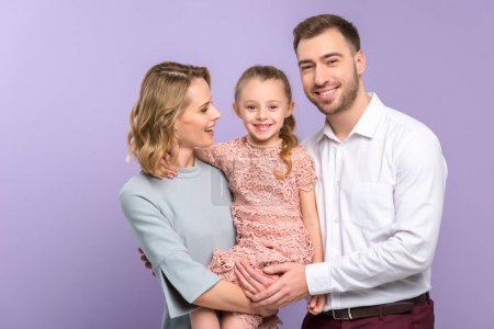 Adorable family embracing with daughter on violet background