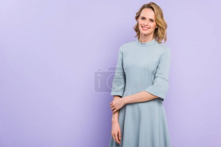 Smiling blonde woman isolated on violet