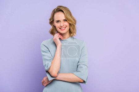 Young blonde woman with hand near face isolated on violet