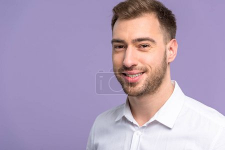 Smiling young man isolated on violet