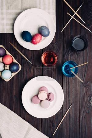 Easter eggs and macarons on plate on wooden table