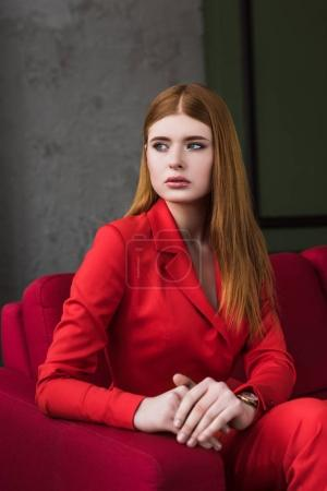 Stylish young woman with wristwatch dressed in red suit