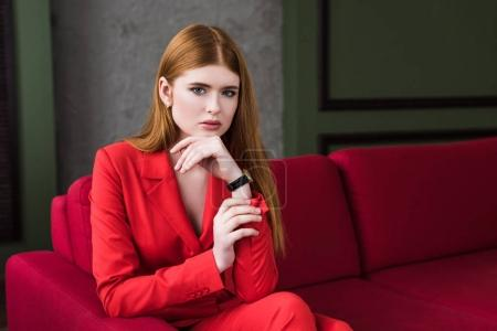 Portrait of young female model with wristwatch sitting on couch
