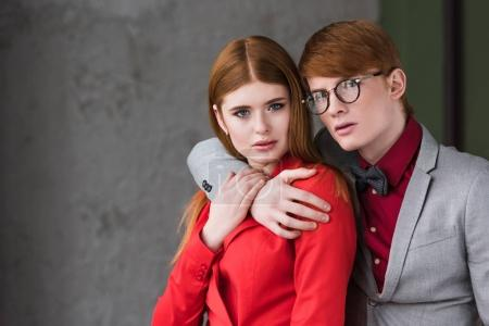 Male fashion model with eyeglasses holding hand on his girlfriend