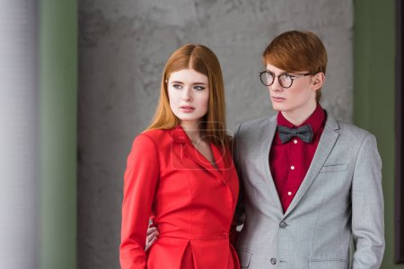 Young male fashion model in eyeglasses and bow tie holding girlfriend waist