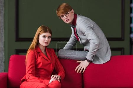 Couple of young fashion model dressed in suits on couch