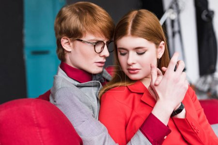 Young male fashion model in eyeglasses holding girlfriend hand