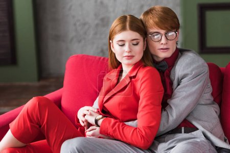 Stylish male in eyeglasses hugging his girlfriend