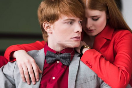 Portrait of young stylish man in bow tie and female with wristwatch
