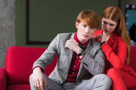 Young male fashion model with girlfriend sitting on couch