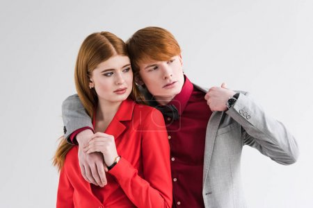 Young couple of fashion models with wristwatches isolated on grey