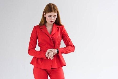 Joven mujer elegante vestida de traje mirando reloj de pulsera aislado en gris